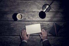Draufsicht eines Geschäftsmannes, der spät an seinem Schreibtisch durch das Licht arbeitet Lizenzfreie Stockfotografie