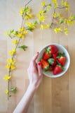 Draufsicht eines Holztischs mit Blumendekoration und der Hand einer Frau, die für eine Schüssel köstliche frische Erdbeeren errei Stockfotos