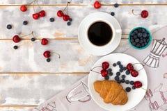 Draufsicht eines köstlichen Frühstücks mit Hörnchen, Kaffee und Blaubeeren und Kirsche auf dem Tisch Lizenzfreie Stockbilder