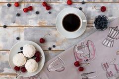 Draufsicht eines köstlichen Frühstücks mit Hörnchen, Kaffee und Blaubeeren und Kirsche auf dem Tisch Lizenzfreies Stockfoto