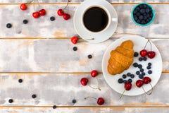 Draufsicht eines köstlichen Frühstücks mit Hörnchen, Kaffee und Blaubeeren und Kirsche auf dem Tisch Lizenzfreie Stockfotografie