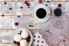 Draufsicht eines köstlichen Frühstücks mit Hörnchen, Kaffee und Blaubeeren und Kirsche auf dem Tisch Stockfotos