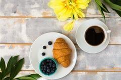 Draufsicht eines köstlichen Frühstücks mit Hörnchen, Kaffee und Blaubeeren und Pfingstrosen auf dem Tisch Lizenzfreie Stockfotografie