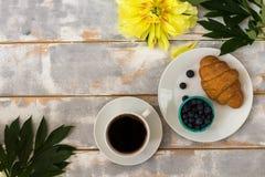 Draufsicht eines köstlichen Frühstücks mit Hörnchen, Kaffee und Blaubeeren und Pfingstrosen auf dem Tisch Lizenzfreie Stockfotos