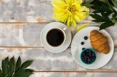 Draufsicht eines köstlichen Frühstücks mit Hörnchen, Kaffee und Blaubeeren und Pfingstrosen auf dem Tisch Lizenzfreie Stockbilder