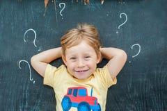 Draufsicht eines kleinen blonden Kinderjungen mit Fragezeichen auf Tafel Konzept für Verwirrung, Brainstorming und Wahl Lizenzfreie Stockbilder