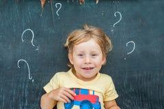 Draufsicht eines kleinen blonden Kinderjungen mit Fragezeichen auf Tafel Konzept für Verwirrung, Brainstorming und Wahl Stockfoto
