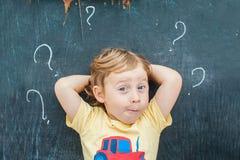 Draufsicht eines kleinen blonden Kinderjungen mit Fragezeichen auf Tafel Konzept für Verwirrung, Brainstorming und Wahl Stockfotos