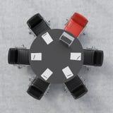 Draufsicht eines Konferenzsaales Ein schwarzer Rundtisch, sechs Stühle, eins von ihnen ist rot Ein Laptop und fünf Papiere Lizenzfreies Stockfoto
