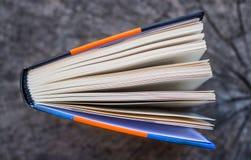 Draufsicht eines offenen Buches auf einem hölzernen Brett Stockbilder