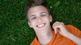 Draufsicht eines Teenagers, der auf den stillstehenden und zufällig lachenden Grasrasen legt stock video footage