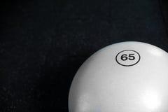 Draufsicht eines weißen Eignungsballs auf einem schwarzen Bodenhintergrund Pilates und gymnastisches Training Aktives Lebensstilk Stockbild