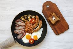 Draufsicht, englisches Frühstück in einer Wanne mit Spiegeleiern, Speck, Bohnen, Würste und Toast auf einem Weiß hölzern Lizenzfreie Stockbilder