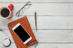 Draufsicht/flache Lage das Stift-/Anmerkungsbuch/weißer Handy/hörende Radiomusik lizenzfreie stockbilder