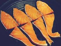 Draufsicht frische rohe Lachse auf schwarzen Tellerfischen stockbilder