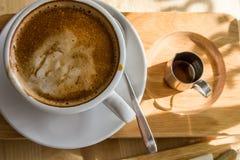 Draufsicht-Kaffeetasse der Nahaufnahme mit süßem Sirup dazu auf hölzernem stockbilder