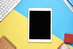 Draufsicht, moderner Arbeitsplatz mit Laptop und Tablette mit dem intelligenten Telefon gesetzt auf einen gelben und blauen Paste Lizenzfreie Stockfotografie