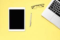 Draufsicht, moderner Arbeitsplatz mit Laptop und Tablette mit dem intelligenten Telefon gesetzt auf einen gelben Pastellhintergru Stockbilder