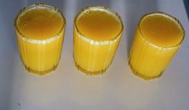 Draufsicht oder unterschiedliche Ansicht des frischen und gesunden Orangensaftes füllten drei Glas auf weißer Tabelle stockfoto