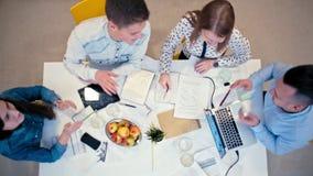Draufsicht - Schreibtisch mit Geräten und Papieren beim Geschäftstreffen des Arbeits-Teams stock footage