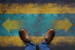 Draufsicht, Stand über Pfeil-Zeichen auf dem Schmutz-Boden, Entscheidung treffend Stockbilder