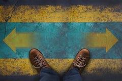 Draufsicht, Stand über Pfeil-Zeichen auf dem Schmutz-Boden, Entscheidung treffend Lizenzfreies Stockfoto