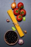 Draufsicht: Teigwaren oder italienische Spaghettis auf schwarzem Steinschieferhintergrund Stockbild