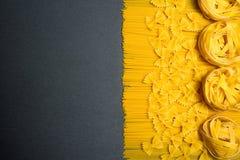 Draufsicht: Teigwaren oder italienische Spaghettis auf schwarzem Steinschieferhintergrund Kopieren Sie Platz Stockfoto
