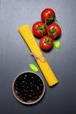 Draufsicht: Teigwaren oder italienische Spaghettis, Tomaten, Oliven und Oregano auf schwarzem Steinschieferhintergrund Stockfotos