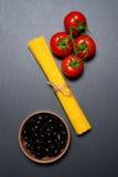 Draufsicht: Teigwaren oder italienische Spaghettis, Tomaten und Oliven auf schwarzem Steinschieferhintergrund Lizenzfreie Stockfotos