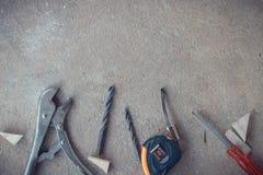 Draufsicht, Tischlerarbeitsbereich mit vielen Werkzeugen auf staubigem konkretem Boden, Handwerkerwerkzeugsatz Stockfoto