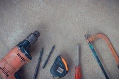 Draufsicht, Tischlerarbeitsbereich mit vielen Werkzeugen auf staubigem konkretem Boden, Handwerkerwerkzeugsatz Lizenzfreie Stockfotografie