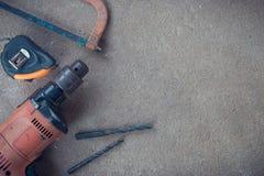 Draufsicht, Tischlerarbeitsbereich mit vielen Werkzeugen auf staubigem konkretem Boden, Handwerkerwerkzeugsatz Lizenzfreies Stockfoto