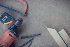 Draufsicht, Tischlerarbeitsbereich mit vielen Werkzeugen und Holz auf staubigem konkretem Boden, Handwerkerwerkzeugsatz Stockbild