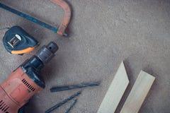 Draufsicht, Tischlerarbeitsbereich mit vielen Werkzeugen und Holz auf staubigem konkretem Boden, Handwerkerwerkzeugsatz Lizenzfreie Stockfotografie