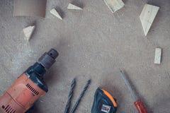 Draufsicht, Tischlerarbeitsbereich mit vielen Werkzeugen und Scantling auf staubigem konkretem Boden, Handwerkerwerkzeugsatz Lizenzfreies Stockbild
