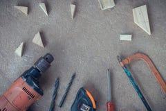 Draufsicht, Tischlerarbeitsbereich mit vielen Werkzeugen und Scantling auf staubigem konkretem Boden, Handwerkerwerkzeugsatz Lizenzfreie Stockfotos