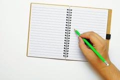 Draufsicht- und Kopienraum, a-Hand, die einen grünen Bleistift, versuchend, etwas auf ein Buch zu schreiben hält Stockfotos