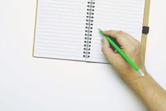 Draufsicht- und Kopienraum, a-Hand, die einen grünen Bleistift, versuchend, etwas auf ein Buch zu schreiben hält Lizenzfreie Stockfotos