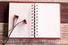 Draufsicht und warmer Ton Kopfhörer, der auf leeres Notizbuch rotes c sich setzt Stockbild