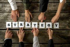 Draufsicht von acht Geschäftsleuten, die das Wort STRATEGIE zusammenbauen Lizenzfreie Stockfotografie
