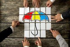 Draufsicht von acht männlichen Händen, die einen bunten Regenschirmesprit zusammenbauen Stockbilder