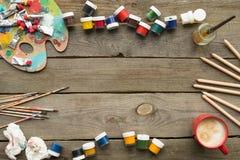Draufsicht von Behältern mit Plakatfarben und von Bürsten auf einem hölzernen Lizenzfreies Stockbild
