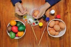 Draufsicht von bunten Ostereiern werden mit Malerpinsel und Palette vom jungen Mann auf Holztisch gemalt Stockbilder