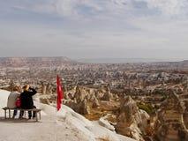 Draufsicht von Cappadocia zwei Frauen sitzen auf Spitze und Blick an der Stadt stockfoto