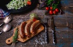 Draufsicht von colorfuls briet Würste und Gemüse auf einem rustikalen Holztisch Würste auf der Grillwanne auf dem hölzernen Hinte Stockfoto