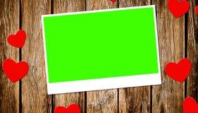 Draufsicht von dekorativen roten Herzen mit Fotorahmen mit Farbenreinheitsschlüssel-Grünschirm auf altem hölzernem Hintergrund Lizenzfreies Stockfoto