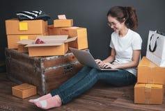Draufsicht von den Frauen, die Laptop-Computer vom Haus auf Bretterboden mit Postpaket, on-line-Ideenkonzept verkaufend Arbeits s lizenzfreie stockfotos
