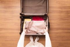 Draufsicht von den Frauenhänden, die einen rosa Blazer in einem Gepäckkoffer für eine neue Reise verpacken stockfoto