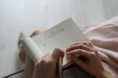Draufsicht von den Frauenhänden, die Ziel für neues Jahr oder Weihnachten schreiben lizenzfreies stockbild